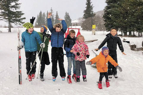 From left to right, Reid Rauch, Ellis Lorentz, Sawyer Johnson, Wylder Johnson, Selma Johnson, Renn Lorentz and Che Lorentz celebrate at the Ski Your Age event held Dec. 26, 2020 at the Lookout Mountain Trails near Homer, Alaska. (Photo by Lila Johnson)