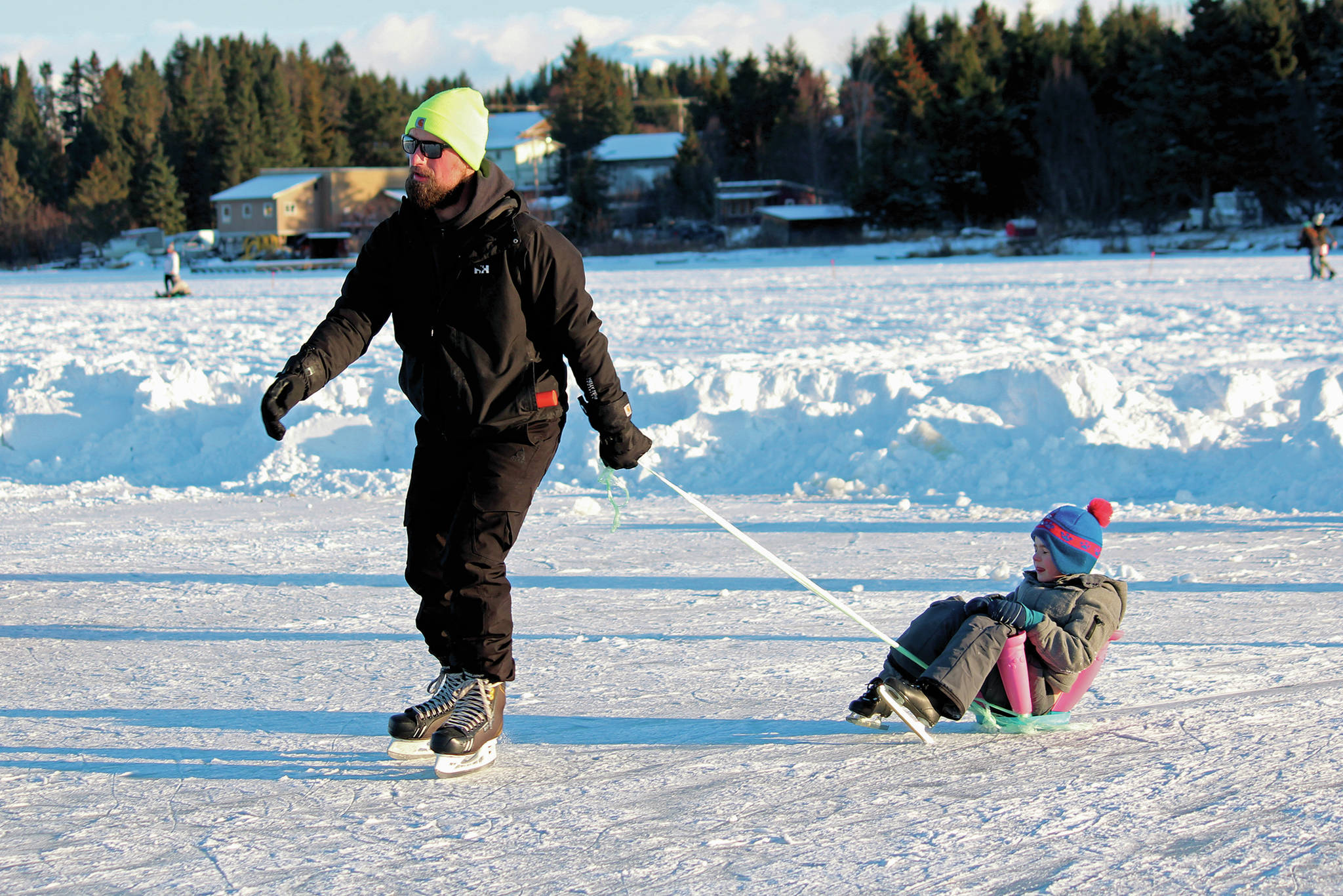 Phil Basargin 5-year-old Maxim Basargin around the ice Saturday, Feb. 6, 2021 during the Skate the Lake event on Beluga Lake in Homer, Alaska. The free skating event was hosted for the community by the Homer Hockey Association. (Photo by Megan Pacer/Homer News)
