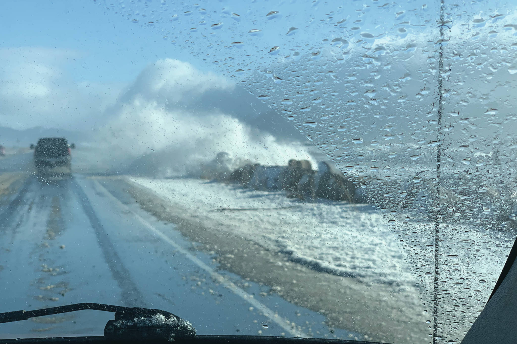 Waves during an extreme high tide and big seas pound the Homer Spit on Sunday afternoon, Feb. 28, 2021, on the Homer Spit, as seen through photographer Malia Anderson's windshield. (Photo by Malia Anderson / Homer News)