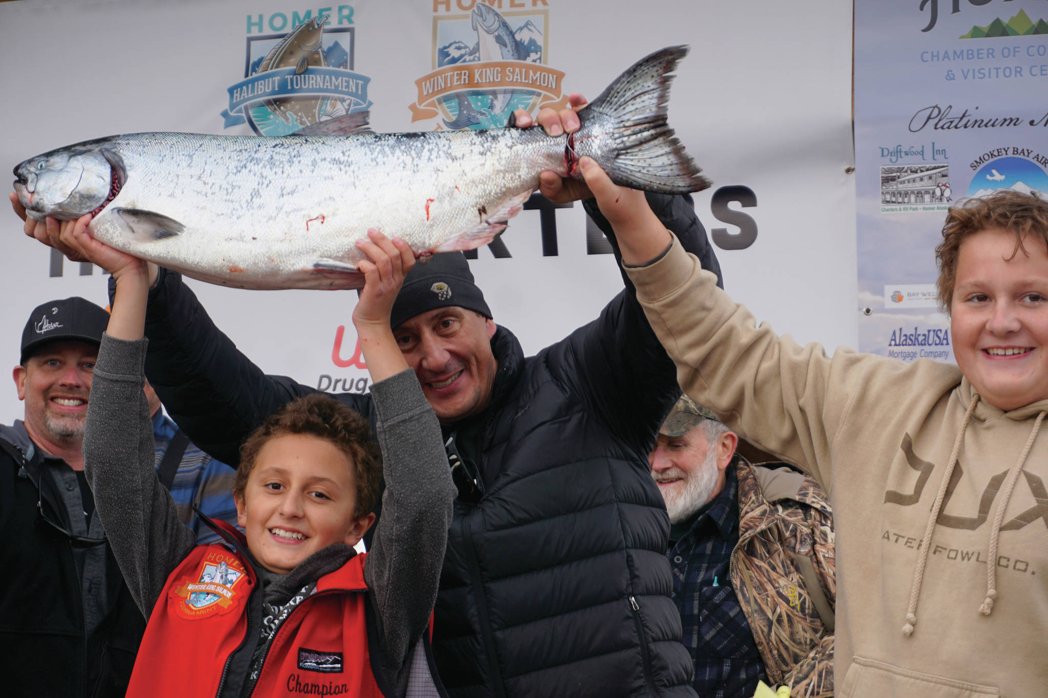 Andrew Marley, the 2021 Homer Winter King Salmon Tournament winner, at left, holds his prize winning 25.62-pound white king salmon on Saturday, April 17, 2021, on the Homer Spit in Homer, Alaska. Helping him are his father, Jay Marley, center, and older brother Weston Marley, right. The family team included Erica Marley, not shown, all fishing on the Fly Dough. (Photo by Michael Armstrong/Homer News)