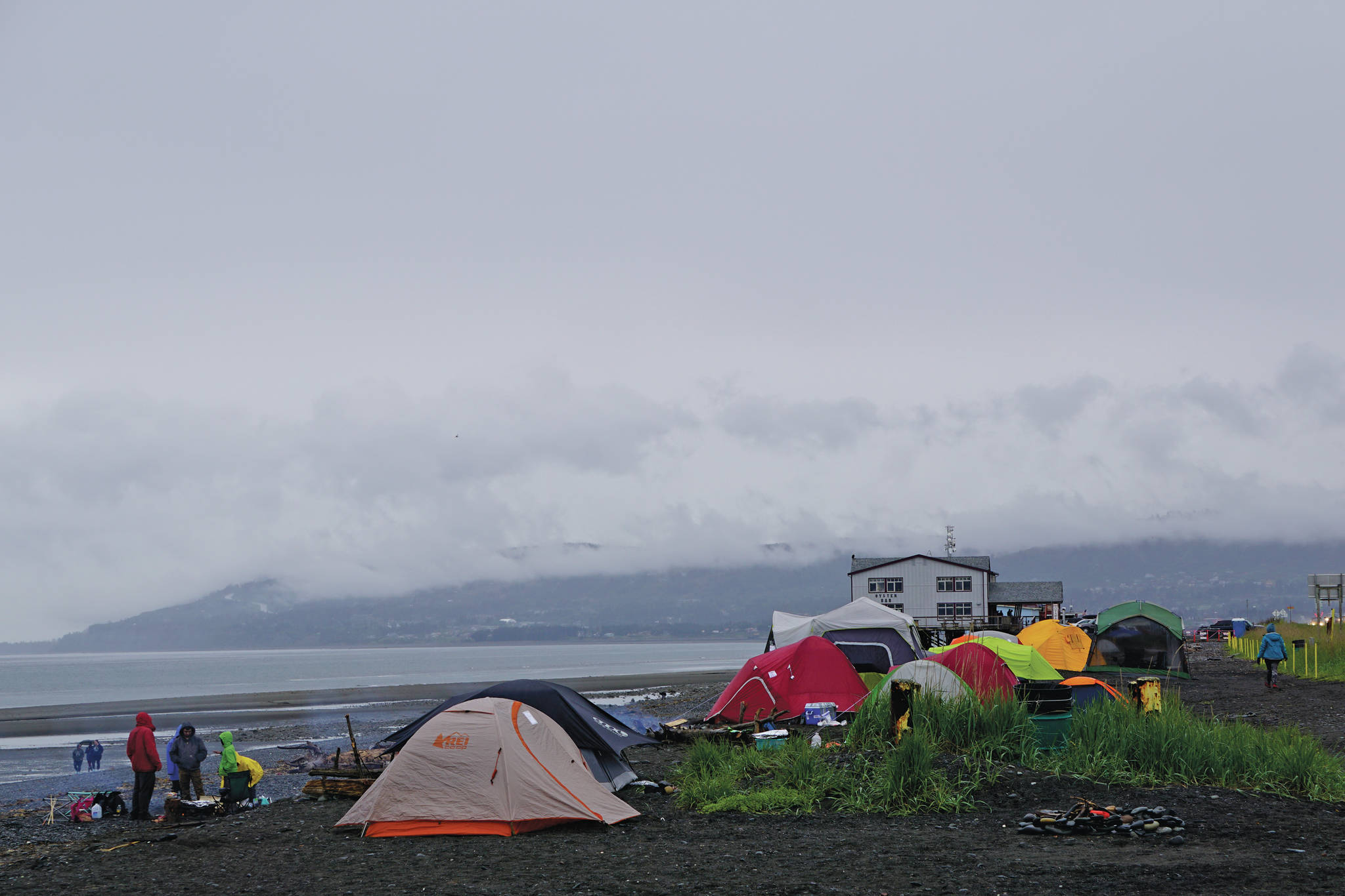 Campers warm up over a bonfire on Saturday, May 29, 2021, on the Homer Spit in Homer, Alaska. (Photo by Michael Armstrong/Homer News)