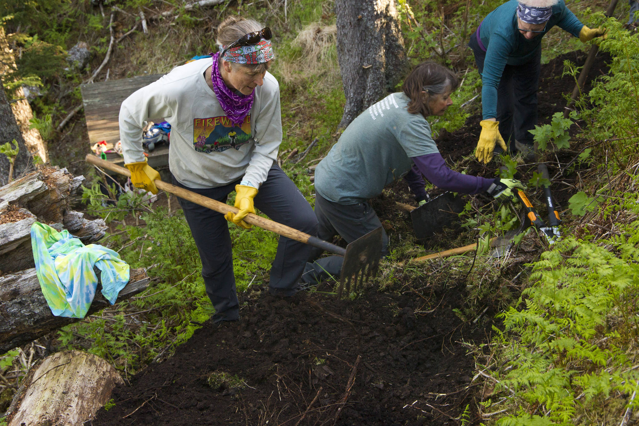 Kathy Sarns, Ruth Dickerson and Lyn Maslow work together to rebuild the trail tread at South Eldred Trail during National Trails Day. (Photo by Sarah Knapp/Homer News)