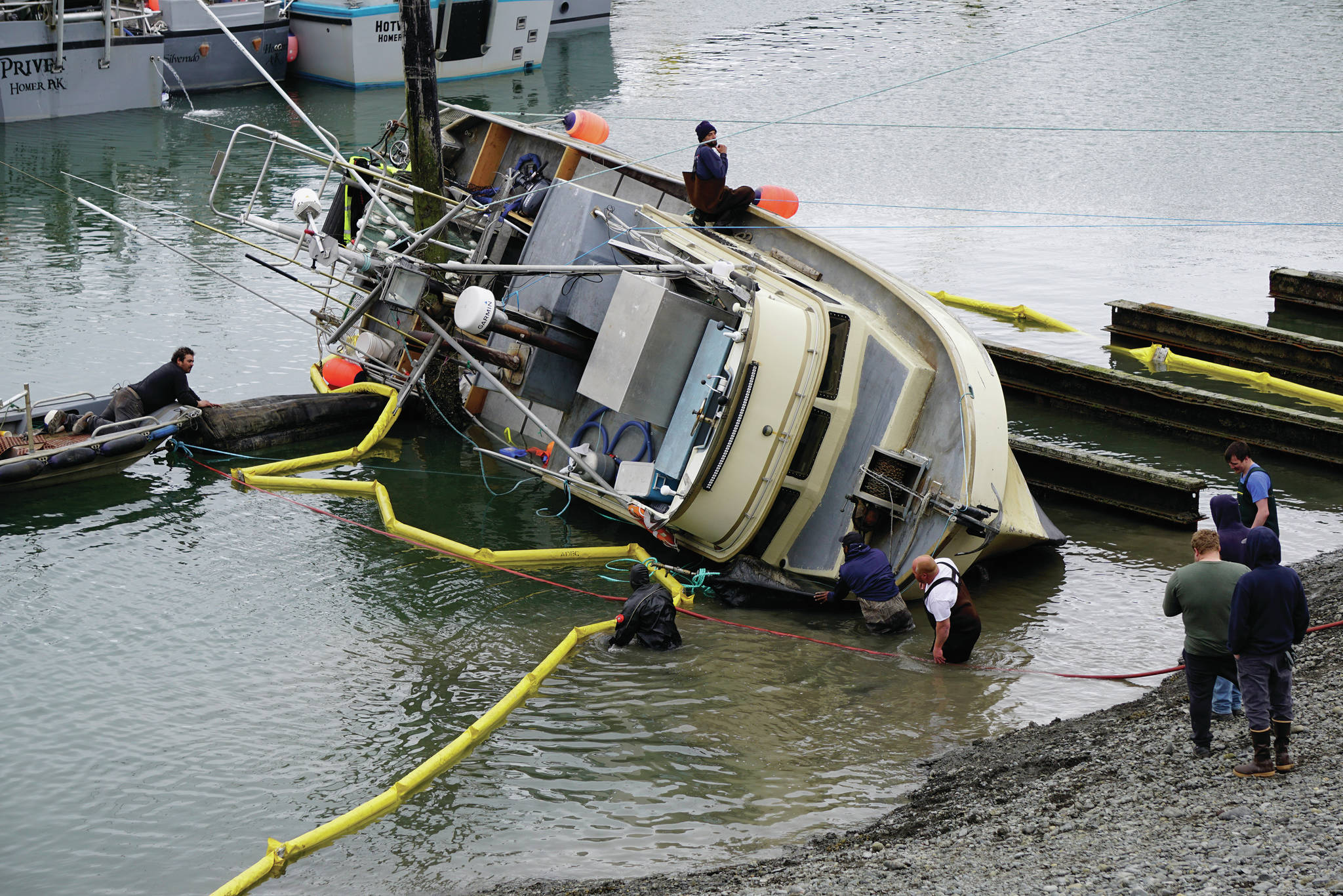 Workers respond to a fishing boat, the F/V Redoubt, that ran aground on the wooden grid on Wednesday, June 2, 2021, in the Homer Harbor in Homer, Alaska. The boat heeled over as the tide went out. (Photo by Michael Armstrong/Homer News)