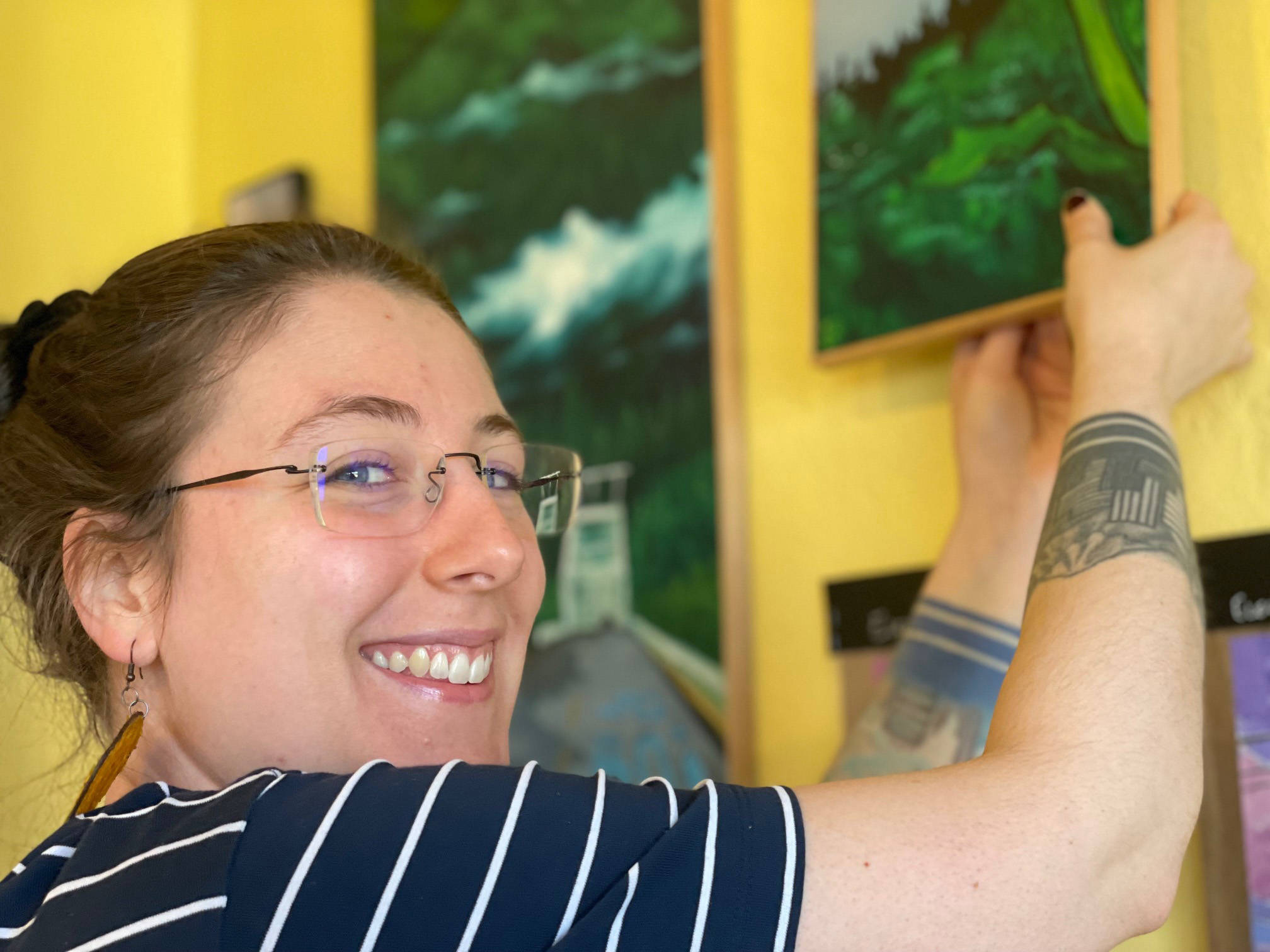 Homer artist Jenna Gerrety straightens paintings currently being shown at Sustainable Wares. (Photo by McKibben Jackinsky)