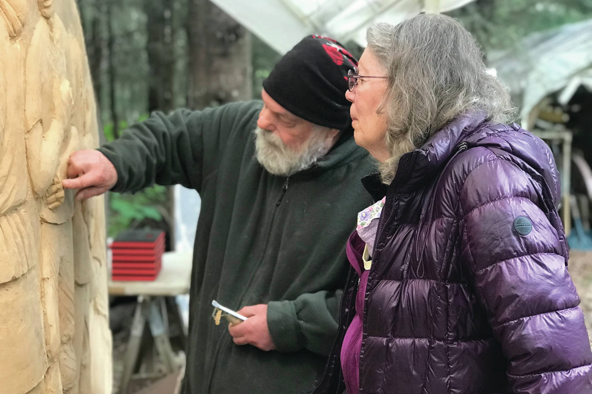 Sara Berg, right, talks with artist Brad Hughes, left, at Hughes' Homer, Alaska, studio in June 2021 about the Loved & Lost Memorial Bench project Berg and other family and friends of Anesha Murnane commissioned to honor Murnane and other missing woman and children. (Photo by Christina Whiting)