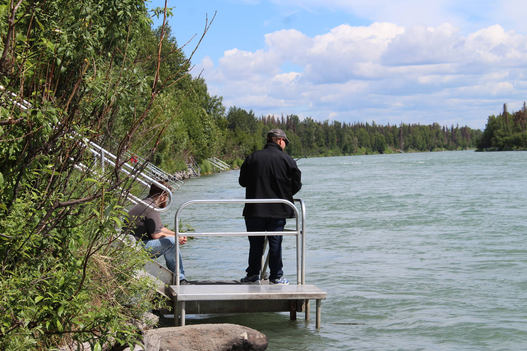 A fisher holds a reel on the Kenai River near Soldotna on June 30, 2021. (Photo by Ashlyn O'Hara/Peninsula Clarion)