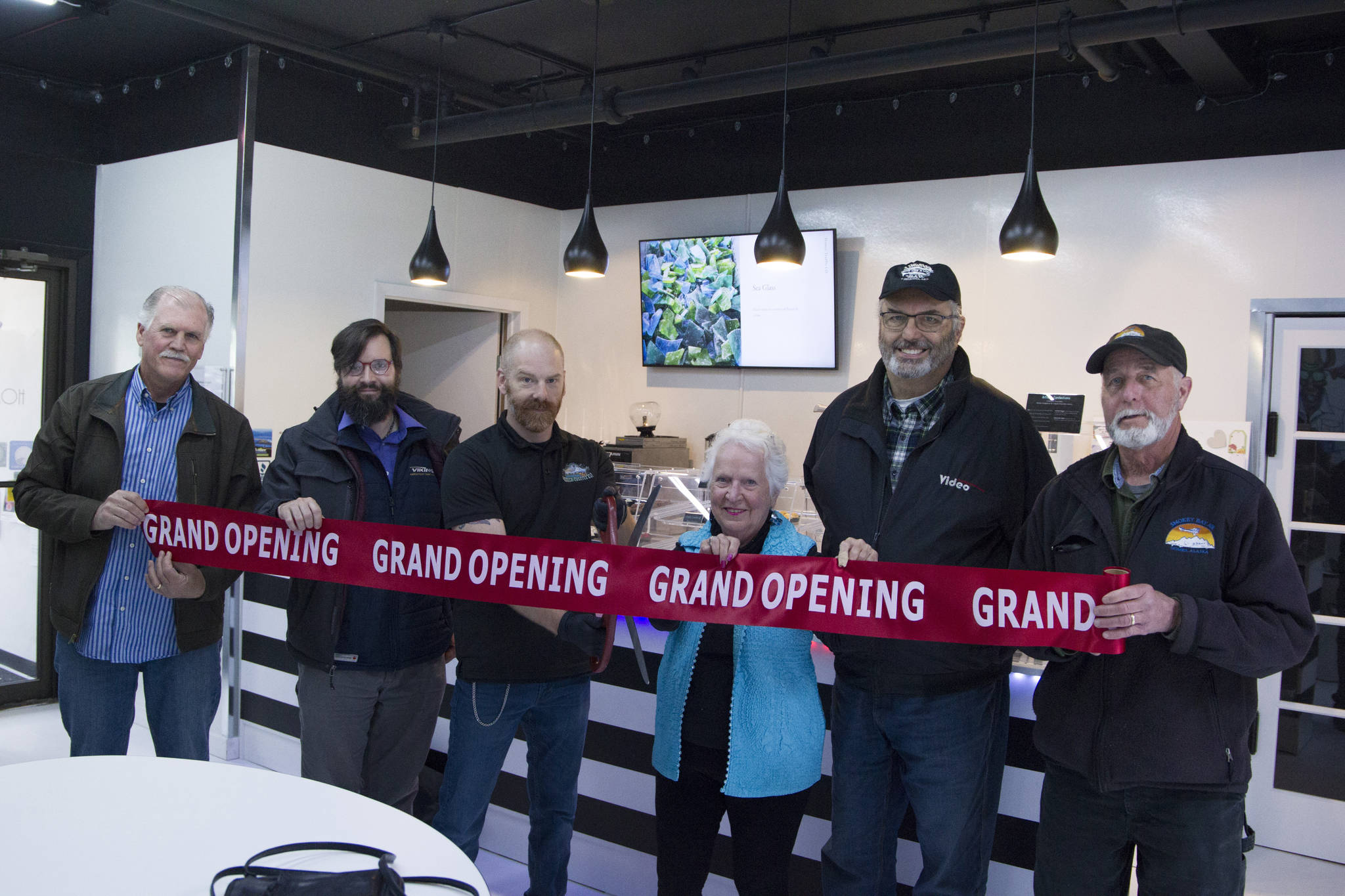 Homer Truffle Co. owner David Briggs cuts the grand opening ribbon at the relaunch of his business on Aug. 17. He is pictured with Homer Chamber of Commerce and Visitor Center board members and employees. (Photo by Sarah Knapp/Homer News)
