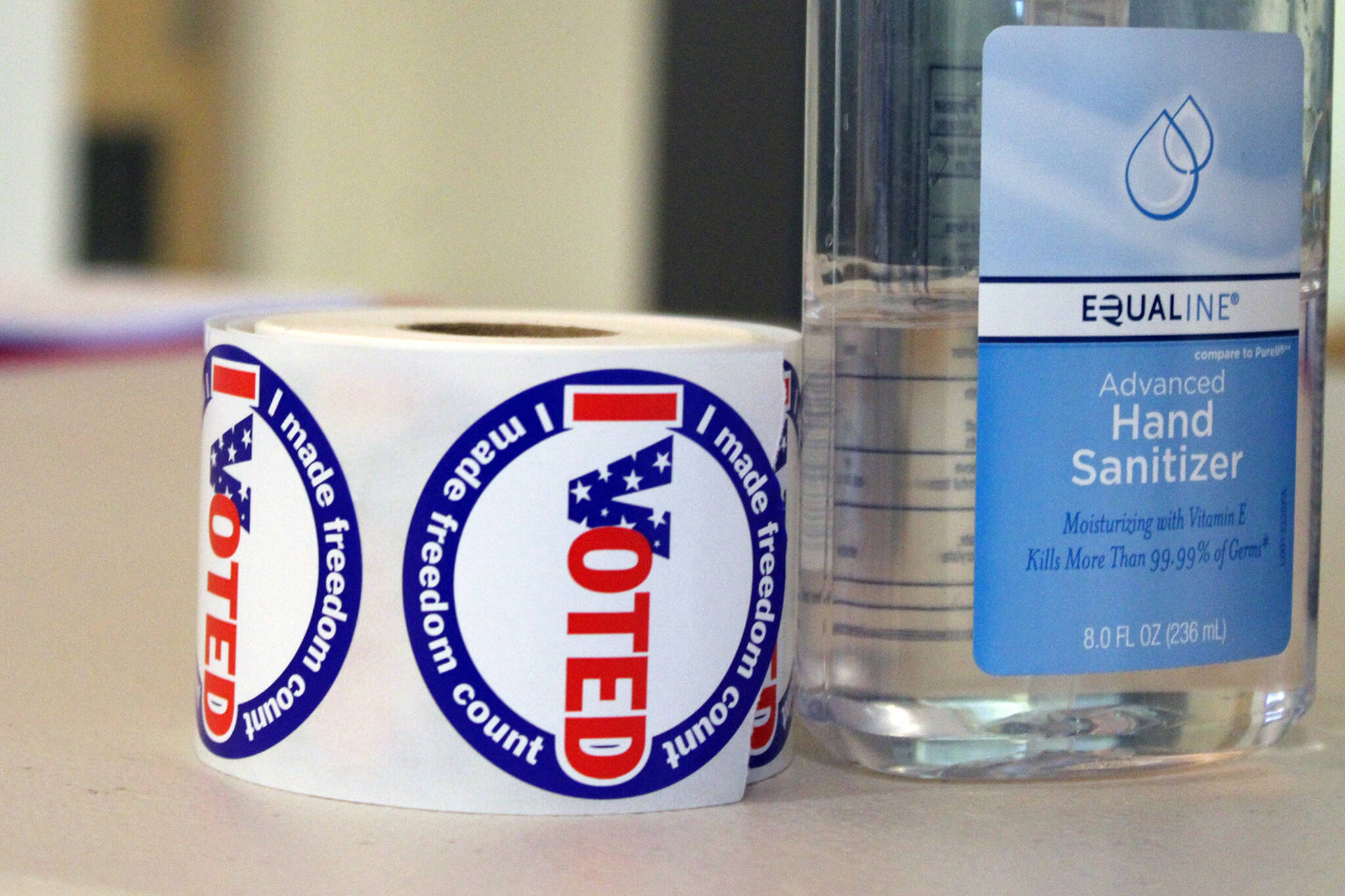 """A roll of """"I Voted"""" stickers sits next to a bottle of hand sanitizer in this October 2020 photo. (Ben Hohenstatt / Juneau Empire)"""