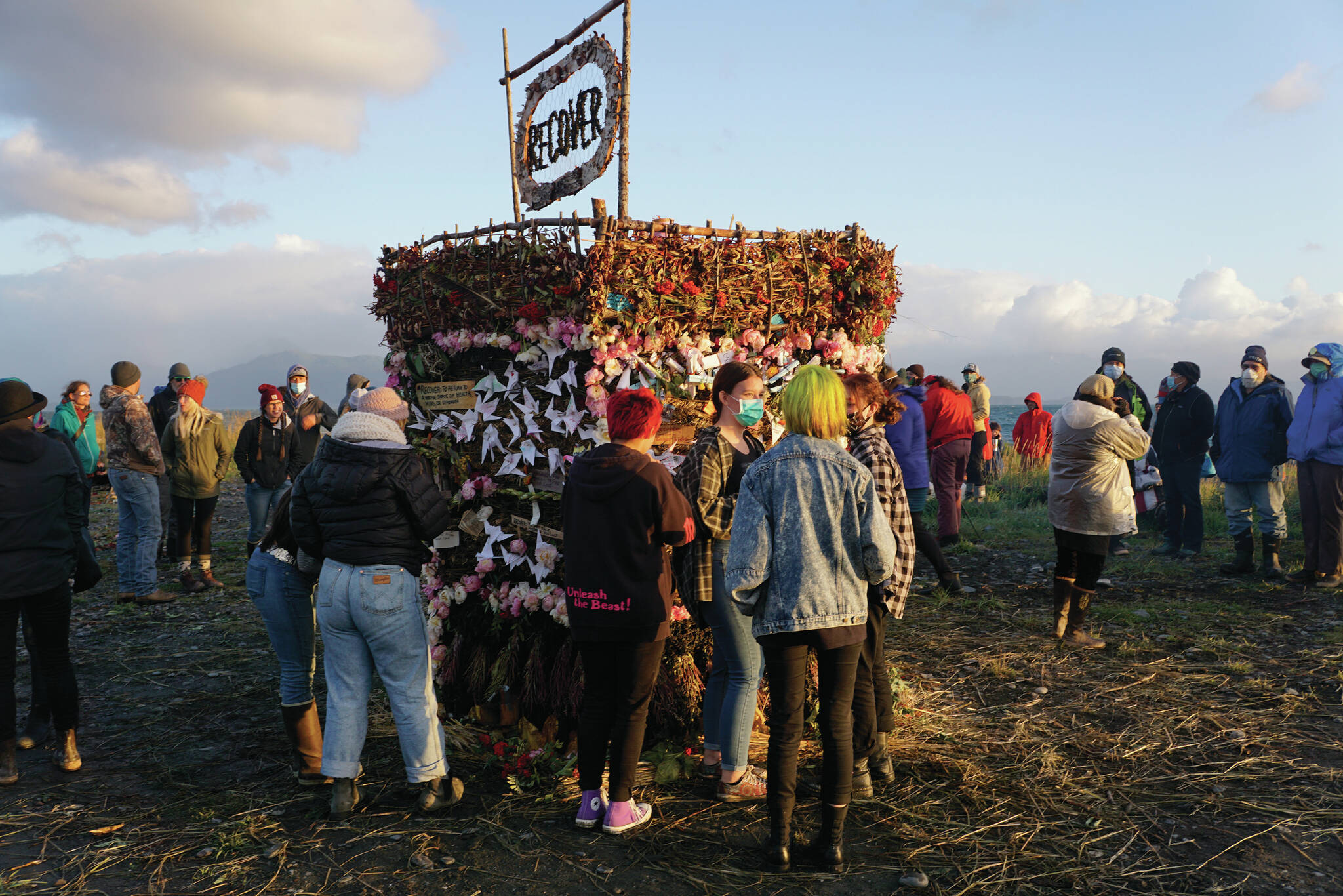 People interact with Recover, the 18th annual Burning Basket, before it's ignited on Sunday, Sept. 12, 2021, at Mariner Park on the Homer Spit in Homer, Alaska. (Photo by Michael Armstrong/Homer News)