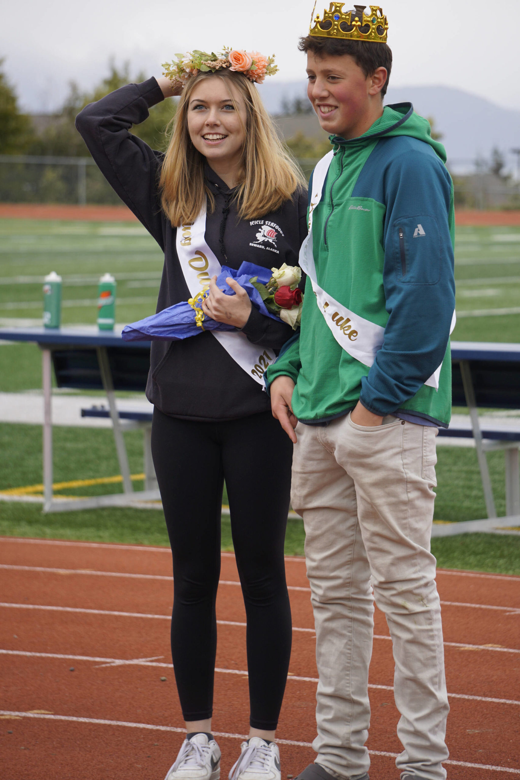 Sophomore class Duchess Minadora Reutov adjusts her crown as Duke Camden Wise watches at the Homer vs. Nikiski junior varsity football game on Saturday, Oct. 2, 2021, at Homer High School. (Photo by Michael Armstrong/Homer News)