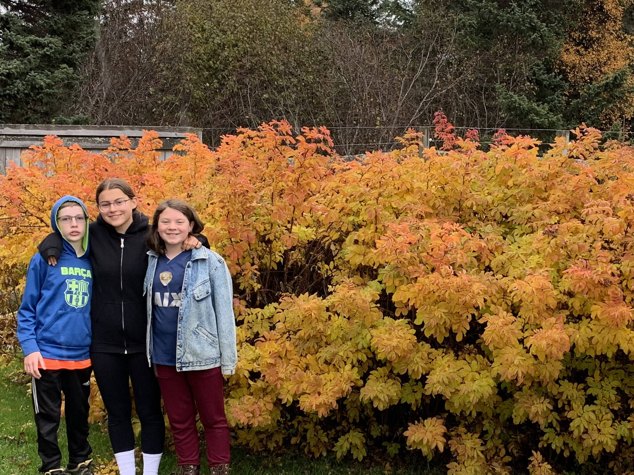 """The """"grands"""" — Luca, Cecilia and Flora — pause on a fall garden walk. (Photo by Rosemary Fitzpatrick)"""